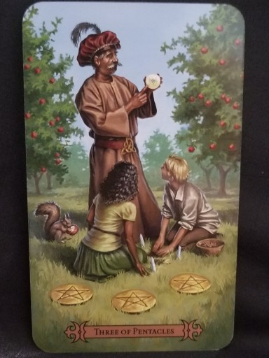 Three of Pentacles - Tarot Card -A magician in a turban giving instructions to a boy and girl sitting at his feet.