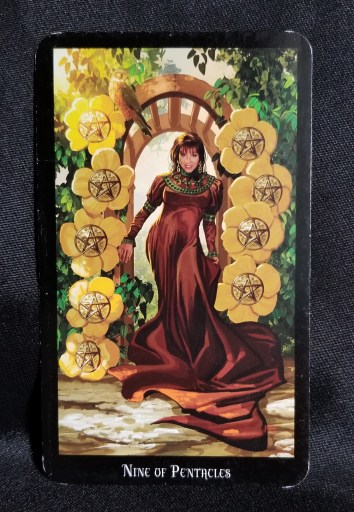 Nine of Pentacle - Tarot Card:  A beautiful woman in a garden.  The arbor she stands under is decorated with nine pentacle discs.