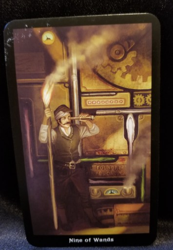 Nine of Wands - Tarot Card:  A man holding a telescope and a torch looking out for trouble.