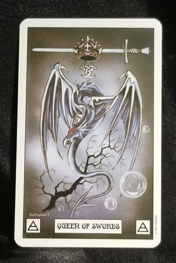 Queen of Swords - Tarot Card:  A gray dragon with a crown run through by a sword hovering over its head.
