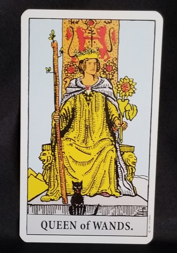 Queen of Wands - Tarot Card:  A Queen sitting on a throne holding a leafy staff in one hand a sunflower in the other.  A black cat sits at her feet.