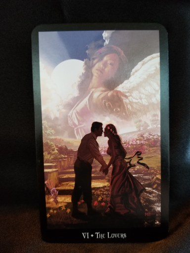 The Lovers - Tarot Card: A man and a woman holding hands, about to kiss, while an angel looksdown over head.