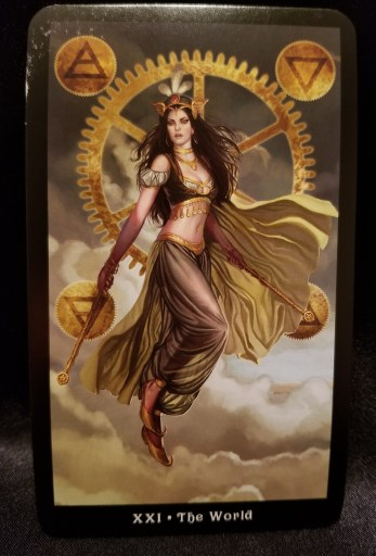 The World - Tarot Card:  A woman dressed like a belly dancer floats in front of a large wheel.  the alchemical symbols for the elements on each of the four corners.