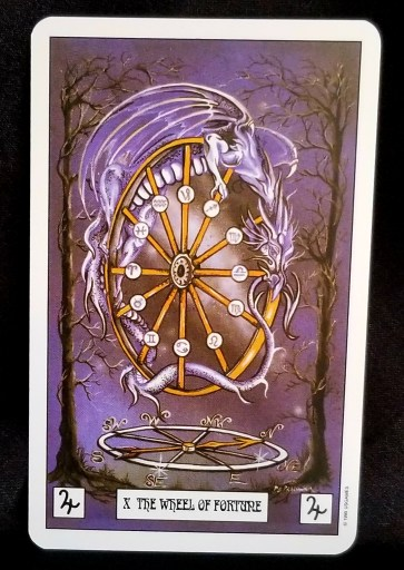 The Wheel of Fortune - Tarot Card:  A lavender dragon holding ont a spinning wheel while coiled in its spokes.  Zodiac symbols are placed on each of the spokes on the wheel.