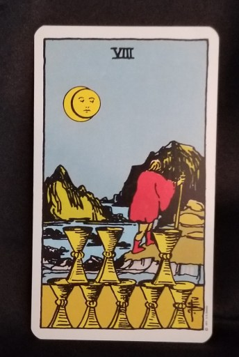 Eight of Cups - Tarot Card: A man with a staff is cautiosly making his way over the rocks next to the ocean.  Eight gold chalices are in the foreground.