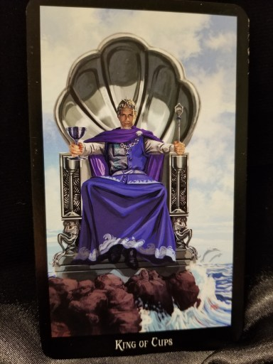 King of Cups - Tarot Card: a King sitting on a shell throne. The throne is sitting atop a rock, next to the ocean.