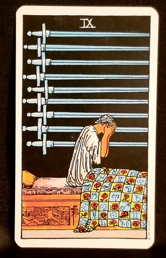Nine of Swords - Tarot Card:  A man sitting up in his bead, holding his hands over hs face in dispair.  Nine swords hang on the wall next to him.