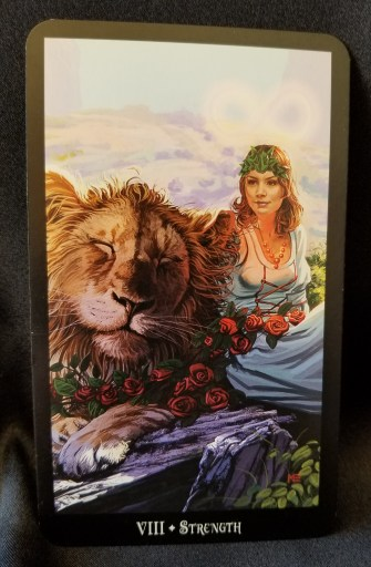 Strength - Tarot Card:  A beautiful woman seated next to a peaceful male lion. The lion has a spray of roses in its paws.