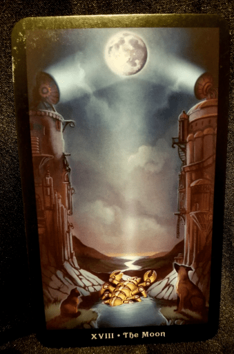 The Moon - Tarot Card: Two pillars flank a stream where a metal lobster is emerging.  On top of the pillars are lights which are illluminating the moon.