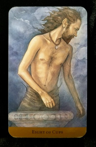 Eight of Cups - Tarot Card:  A shirtless man standing next to a basin of water with moon phases pictured on it.