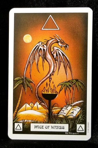 Page of Wands- Tarot Card: A single red-brown dragon hovering over a flaming torch.  A book and quill are on one side and pyramids and a palm tree on the other.