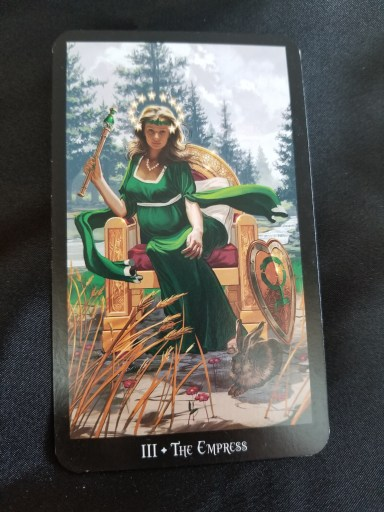 The Empress-Tarot Card: A pregnant woman holding a scepter seated on a throne. A shield and a rabbit are at her feet.