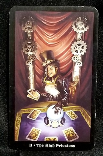 The HIgh Priestess- A wman dressed in steampuk attire seated before a crystal ball and tarot cards.