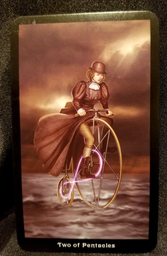 Two of Pentacles-Tarot: A woman in Steampunk attire riding an old-fashioned bicycle.
