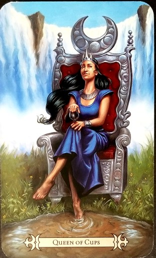 Queen of Cups- A striking woman seated upom a throne.  A crescent moon is over her head and she holds a silver chalice.