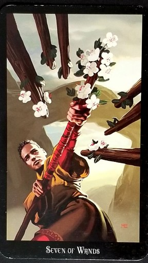 Seven of Wands - A man holding a flowered staff at the ready