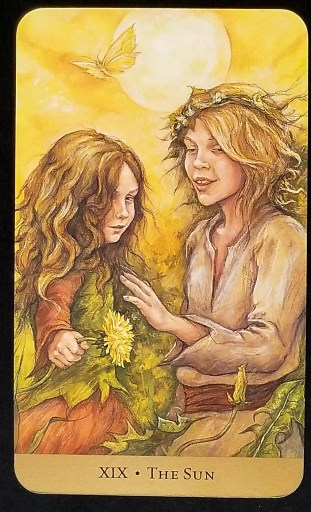 The Sun-Tarot- Two young children holding flowers, looking joyful as they stand in the sunlight.