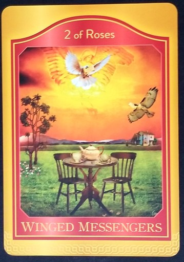 2 of Roses - A Dove and a hawk fly above a table and chairs situated in a meadow.