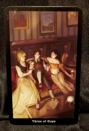 Three of Cups- A man and two women lounge on a settee.  They look relaxed and comfortable