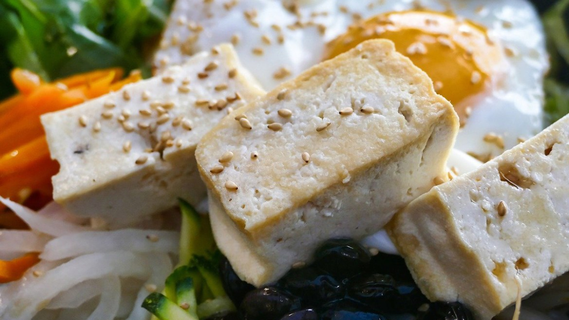 Come fare il tofu in casa: pezzi di tofu al naturale all'interno in un'insalata