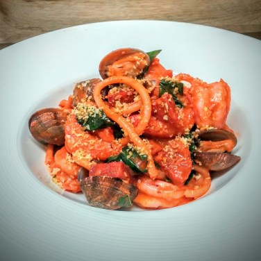 BUCATINI PASTA- sauteed shrimp, clams, Spanish chorizo and basil cooked in a smoked tomato sauce and tossed wiht a fresh bucatini pasta. Finished with olive oil toasted bread crums