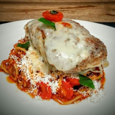 CHICKEN PARMIGIANA - tenderized chicken breast stuffed with fresh herbs mozzarella and Asiago cheeses and crusted in bread crumbs served over spaghtetti pomodoro