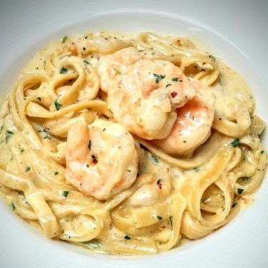 SHRIMP FETTUCCINE ALFREDO - fettuccine pasta simmered in a mild Asiago cream sauce topped with shrimp