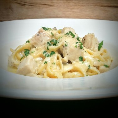 CHICKEN FETTUCCINE ALFREDO - fettuccine pasta simmered in a mild Asiago cream sauce topped with chicken