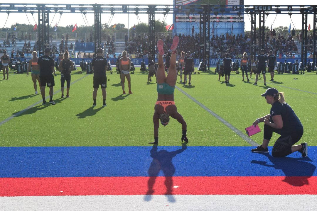 Amanda Barnhart handstand walks across the finish line at the 2019 CrossFit Games