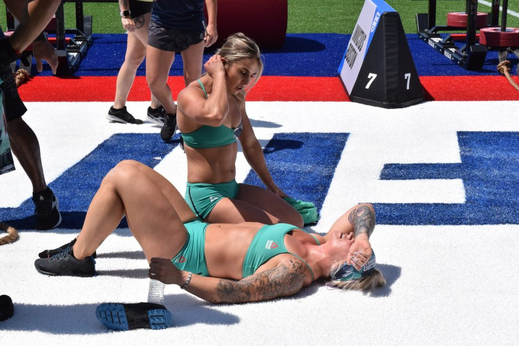 Kaitlyn Kassis of CrossFit Invictus Boston tends to teammate Kelsey Kiel after an 11th-place finish in Team Strongman's Fear.
