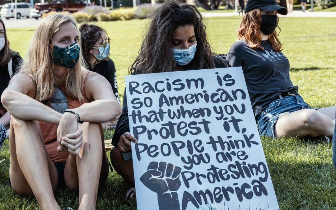 Women protest racial inequality while wearing masks in a park.