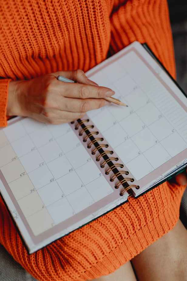 person holding white book planner