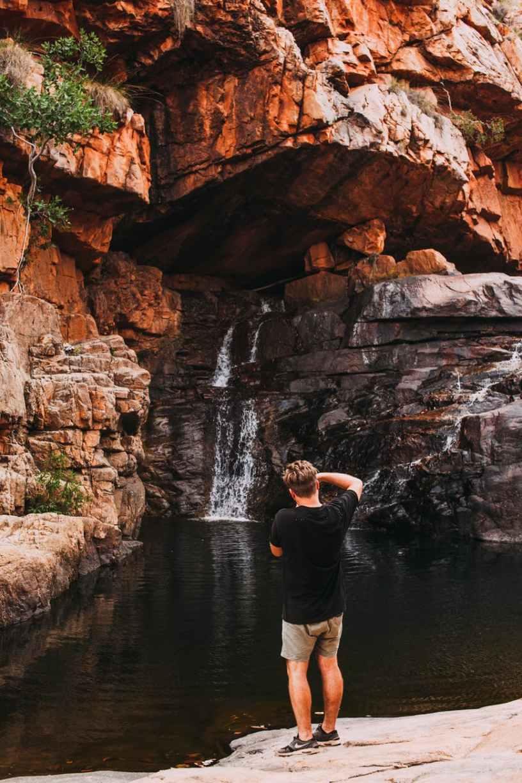 anonymous male explorer admiring waterfall streaming through rocky ravine