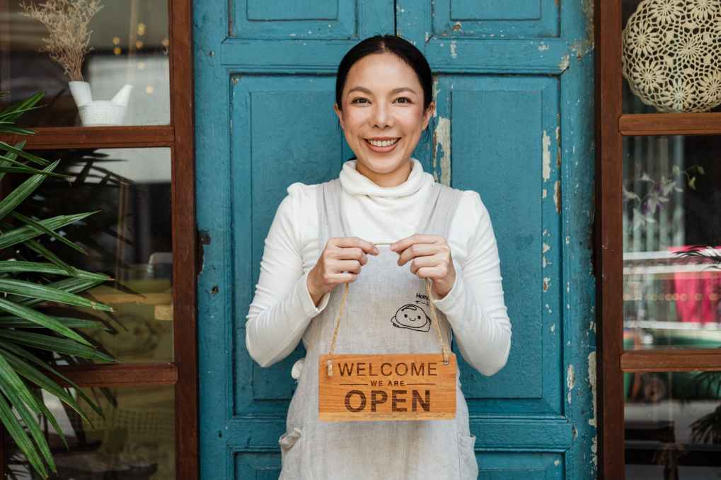ethnic female cafe owner showing welcome we are open inscription