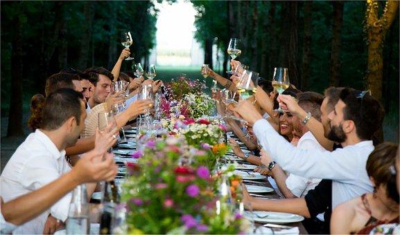 Grupo de invitados a una comida brindando.
