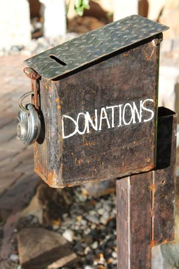 Buzón de metal medio oxidado con un candado con la leyenda de donaciones en ingles.