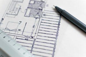 Plano de un proyecto arquitectónico, sobre el cual hay un plumón y una regla de aluminio.