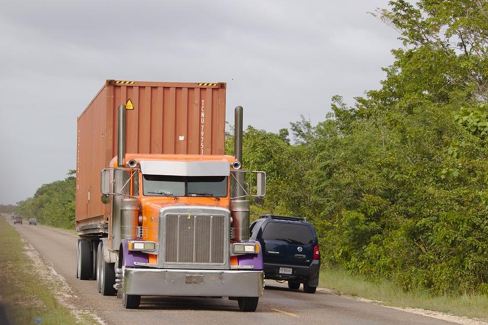 Traíler con contenedor circulando por una carretera.