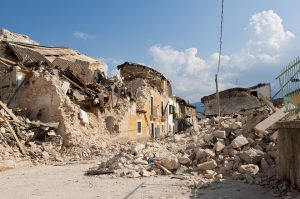 Imagen de una calle devastada por los efectos de un sismo, en la que solo se ven escombros de casa.