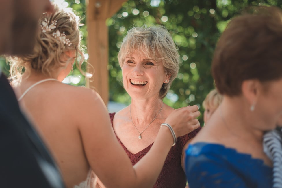mother of the groom smiles while hugging bride