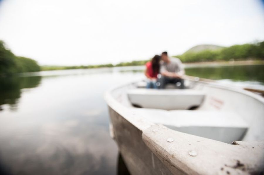 Sally and Terence sit in a boat on a lake in Bear Mountain, NY. Captured by awesome NJ wedding photographer Ben Lau.