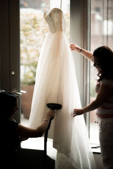 Bridesmaids steam a wedding dress for a wedding at the Eventi Hotel in New York City. Captured by NYC wedding photographer Ben Lau.