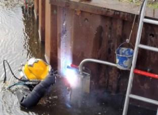 Civiele onderwaterwerken duiker is aan het onderwater lassen