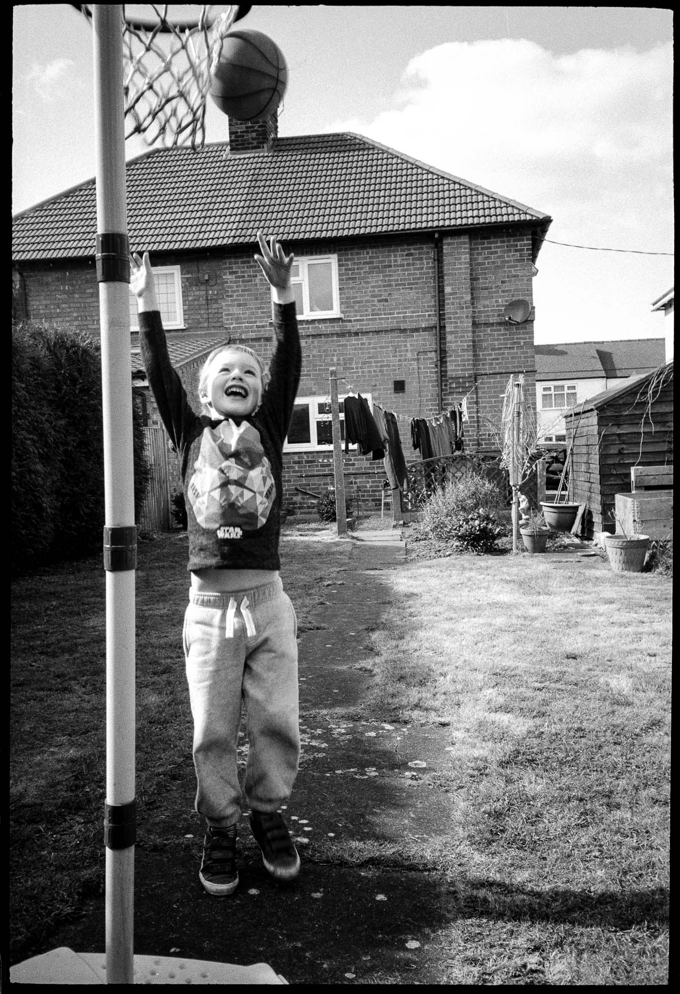 a child playing basketball in the garden, shot in black and white