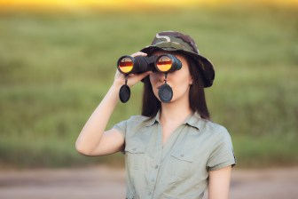 woman with binoculars and a camouflage hat