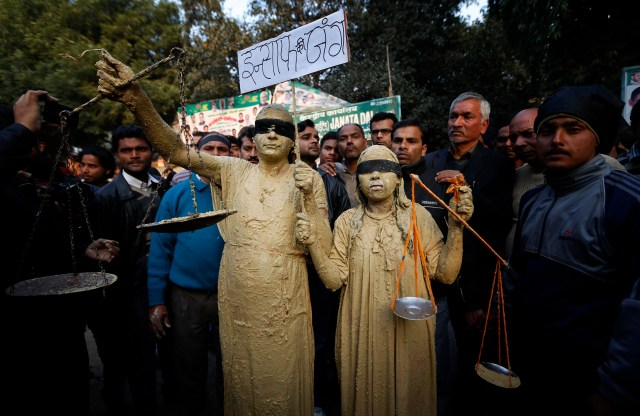 Indian activists, dressed as Lady Justice, protest sexual violence and impunity for attackers