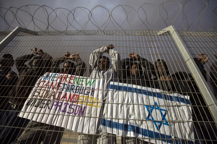 African refugees behind a barbed-wire fence in Israel's Holot detention center in the Negev desert  CREDIT: Reuters