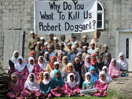 "Accompanying its press release, included a photo of residents with a sign reading ""Why do you want to kill us, Robert Doggart?"""