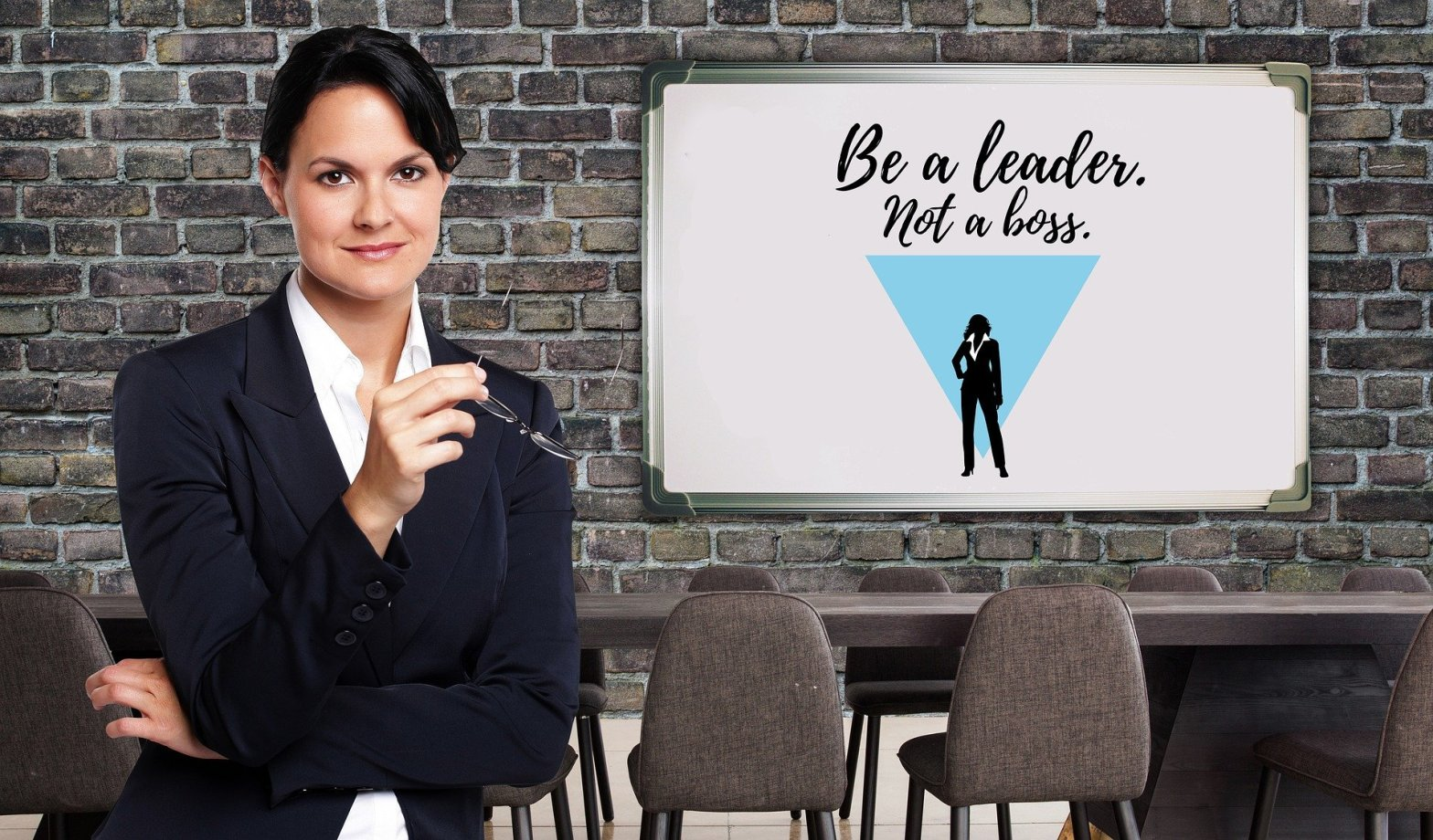A woman stood in front of a board that reads be a leader not a boss