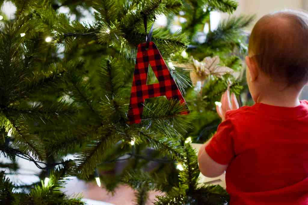 toddler in front of christmas tree with safe ornaments